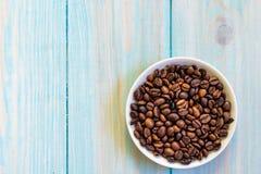 在板材的咖啡豆 在土气浅兰的木背景的平的位置 库存图片