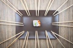 在板材的唯一寿司卷有许多的在木桌上的筷子 图库摄影