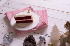在板材的圣诞节蛋糕在木背景和12月的红色织品 免版税图库摄影