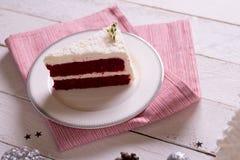 在板材的圣诞节蛋糕在木背景和12月的红色织品 免版税库存照片