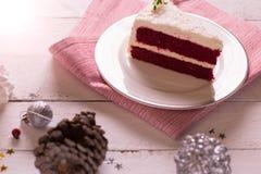 在板材的圣诞节蛋糕在木背景和12月的红色织品 免版税库存图片