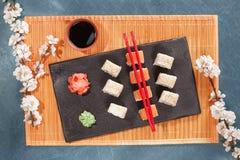 在板材的寿司有筷子、姜、大豆、山葵和佐仓的 免版税库存照片