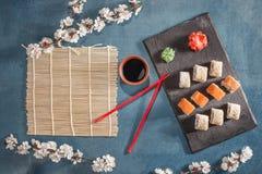 在板材的寿司有筷子、姜、大豆、山葵和佐仓的 图库摄影