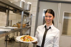 在板材的微笑的女服务员服务沙拉 免版税库存照片