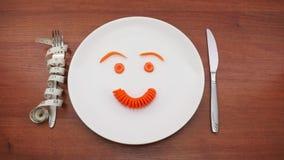 在板材的意思号红萝卜 红萝卜哀伤和快乐的面带笑容在一块白色板材的 停止运动 影视素材