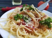 在板材的意粉,叉子吃在黑木背景的开胃蕃茄荷兰芹 库存图片