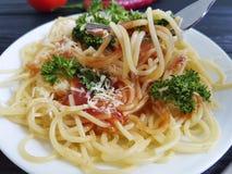 在板材的意粉,叉子吃在黑木背景的部分开胃蕃茄荷兰芹 库存照片