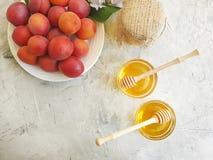 在板材的新鲜的桃子,有机的蜂蜜,在灰色具体背景的虹膜花 免版税库存图片