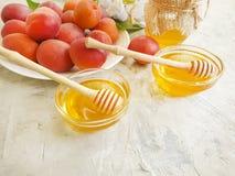 在板材的新鲜的桃子,鲜美蜂蜜晴朗有机,在灰色具体背景的虹膜花 免版税图库摄影