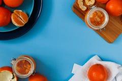 在板材的新鲜的桔子,在蓝色桌上的橙色果酱 复制文本空间 顶视图 免版税库存图片