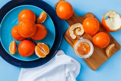 在板材的新鲜的桔子,在蓝色桌上的橙色果酱 顶视图 库存照片
