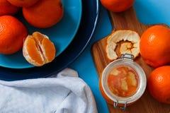 在板材的新鲜的桔子,在蓝色桌上的橙色果酱 顶视图 库存图片