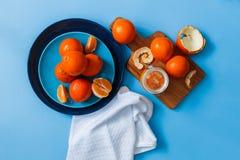 在板材的新鲜的桔子,在蓝色桌上的橙色果酱 顶视图 免版税库存照片