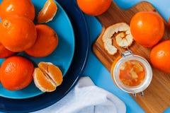 在板材的新鲜的桔子,在蓝色桌上的橙色果酱 顶视图 图库摄影