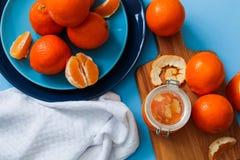 在板材的新鲜的桔子,在蓝色桌上的橙色果酱 顶视图 免版税图库摄影
