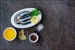 在板材的新鲜的沙丁鱼有油、柠檬、盐和草本的准备好烹调 图库摄影