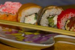 在板材的日本料理和食物棍子在木板条 库存照片