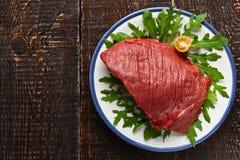 在板材的未加工的红肉在木桌上 库存照片
