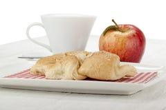 在板材的杏仁新月形面包用苹果和杯子 免版税库存照片