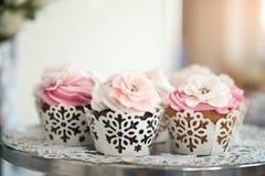 在板材的杯形蛋糕在自助餐桌上 与奶油的五颜六色的美丽的杯形蛋糕 库存图片