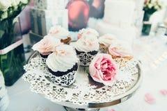 在板材的杯形蛋糕在自助餐桌上 与奶油的五颜六色的美丽的杯形蛋糕 免版税库存照片