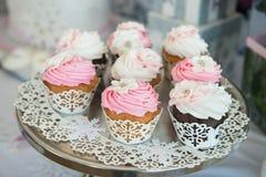 在板材的杯形蛋糕在自助餐桌上 与奶油的五颜六色的美丽的杯形蛋糕 免版税库存图片