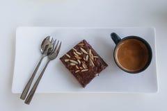 在板材的果仁巧克力蛋糕有咖啡的,在白色桌布 免版税图库摄影