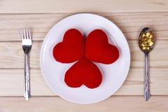 在板材的概念红色心脏有在匙子和叉子的身体补品的 库存照片