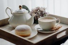 在板材的油炸圈饼在woode上用热的咖啡早餐 库存图片