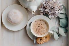 在板材的油炸圈饼在woode上用热的咖啡早餐 图库摄影