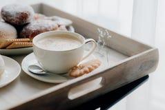 在板材的油炸圈饼在woode上用热的咖啡早餐 库存照片