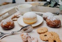 在板材的油炸圈饼在woode上用热的咖啡早餐 免版税库存图片