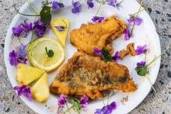 在板材的油煎的面包鱼有花和菠萝的 库存照片