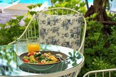 在板材的海鲜面条和橙汁在庭院里浇灌 免版税库存照片