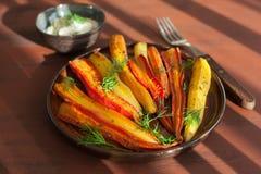 在板材的烤五颜六色的红萝卜 免版税图库摄影