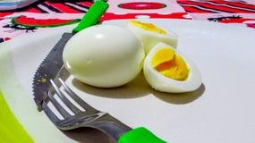 在板材的煮沸的鸡蛋有利器的:叉子和刀子 免版税库存图片