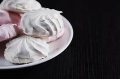 在板材的甜白色和桃红色蛋白软糖 库存图片