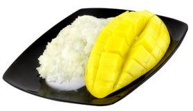 在板材的甜米一个黄色成熟甜beautifulmango果子和芒果切与立方体隔绝了白色背景 免版税库存照片