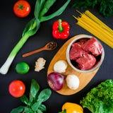 在板材的生肉在木板和新鲜蔬菜在黑暗的背景 顶视图 平的位置 背景许多饺子的食物非常肉 库存图片