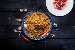 在板材的肉饭和沙拉achichuk有在黑暗的背景的东方装饰品的 中亚烹调- Plov 顶视图 库存照片