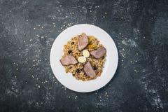 在板材的肉饭有在黑暗的背景的东方装饰品的 中亚烹调- Plov 顶视图 免版税库存照片