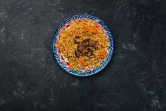 在板材的肉饭有在黑暗的背景的东方装饰品的 中亚烹调- Plov 顶视图 库存图片