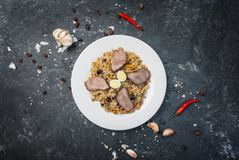 在板材的肉饭有在黑暗的背景的东方装饰品的 中亚烹调- Plov 顶视图 免版税库存图片