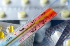 在板材的背景的医疗水银温度表有药片的 图库摄影