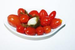 在板材的蕃茄在白色背景用莳萝和一瓣大蒜 免版税库存图片
