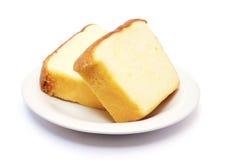 在板材的被切的黄油蛋糕 库存图片