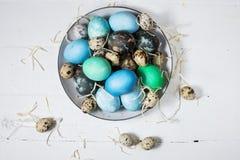 在板材的被绘的鸡蛋、鹌鹑和鸡鸡蛋、油漆和刷子在白色木背景,复活节装饰 免版税库存照片