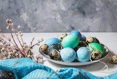 在板材的被绘的鸡蛋、鹌鹑和鸡鸡蛋、油漆和刷子在白色木背景,复活节装饰 库存照片