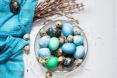 在板材的被绘的鸡蛋、鹌鹑和鸡鸡蛋、油漆和刷子在白色木背景,复活节装饰 库存图片