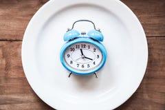 在板材的闹钟 吃时间 免版税库存图片